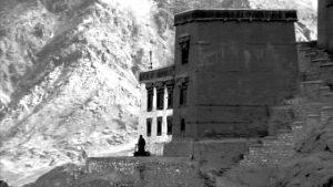 Munk utanför kloster bland höga berg