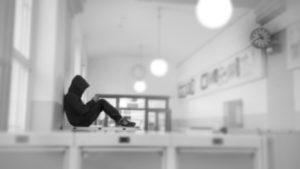 En elev som sitter i en tom korridor