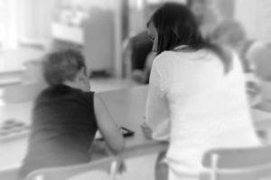 En lärare som sitter bredvid en elev och hjälper till